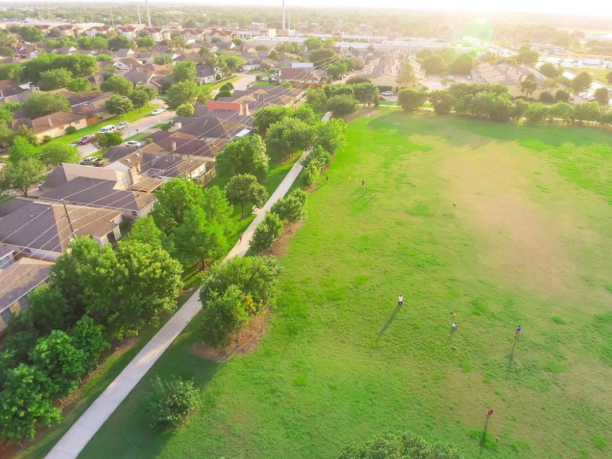 Aerial huge park near residential houses with people playing sport, exercising on green meadow. Green urban recreation surrounds by green tree in Houston, Texas, US.. Tightly packed homes neighborhood